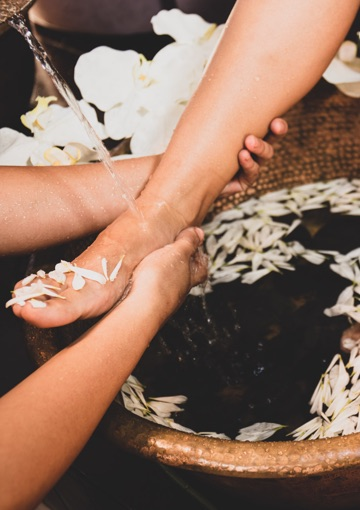 Foot getting wet with flowers and receiving the best service of manicure and pedicure spa