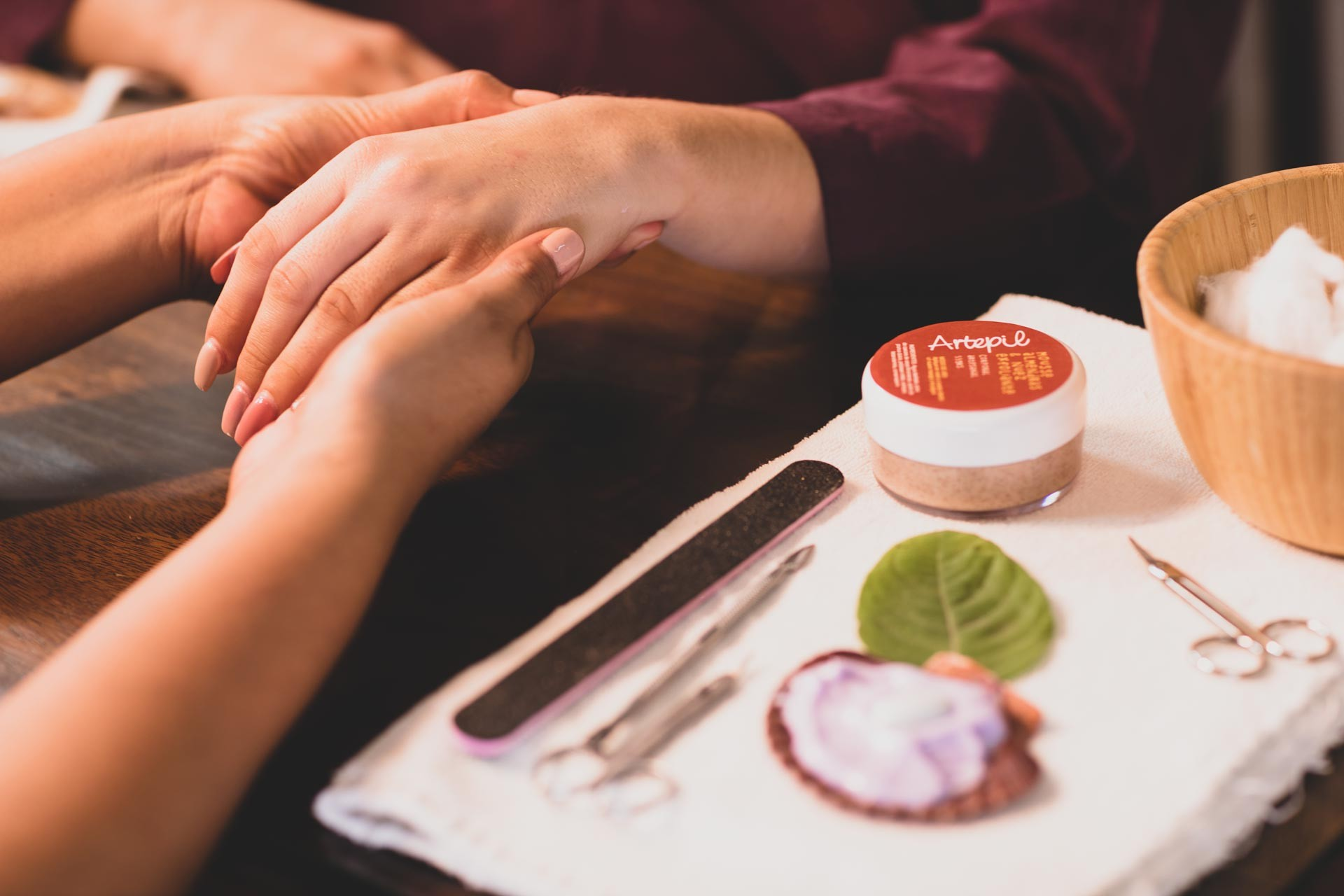 Hands applying manicure services with professional products